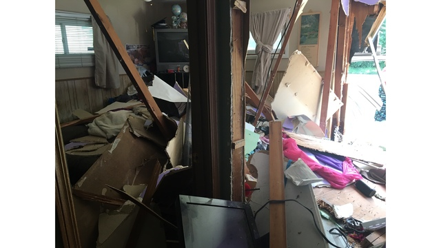 Woman crashes into Topeka home after dropping cigarette while driving
